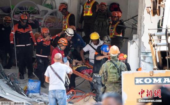 图为菲律宾救援人员在坍塌的建筑现场进行紧张搜救。
