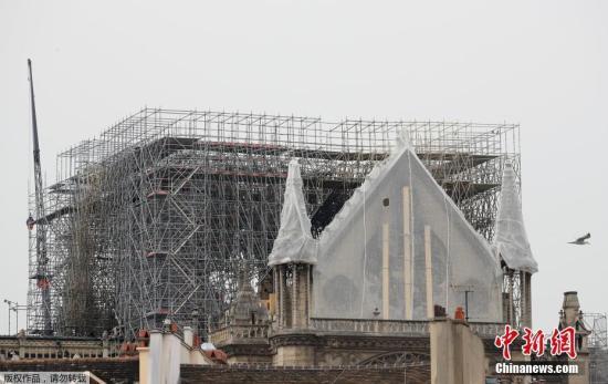 资料图:当地时间4月23日,法国巴黎,工人们为遭大火重创的巴黎圣母院安装了临时防水布,以保护圣母院免受雨水的破坏。