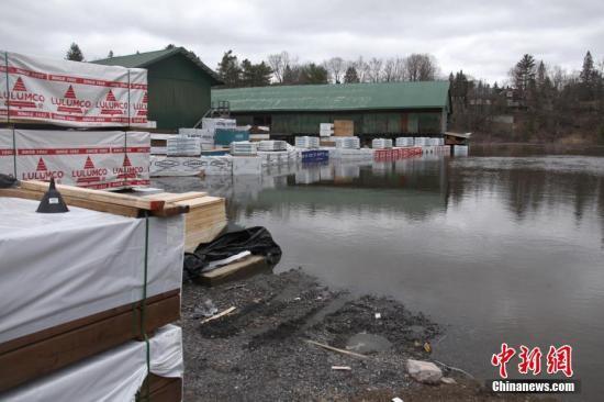 当地时间4月24日,在加拿大多伦多以北大约200公里外的布雷斯布里奇(Bracebridge)镇,春季洪水灾情正愈发严峻,穿城而过的穆斯科卡河水位猛涨。当地市政当局已宣布进入紧急状态。由于近期持续降雨和冰雪融化,加拿大东部安大略省、魁北克省、新不伦瑞克省多地目前正面对洪水挑战。图为河道边一间大型建材店货场的大批建材泡在水中。<a target='_blank' href='http://www.chinanews.com/'>中新社</a>记者 余瑞冬 摄