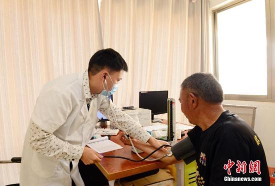 资料图:测量血压。中新社发 尚宇杰 摄