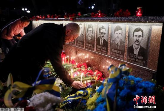 """资料图:当地时间4月26日,乌克兰Slavutich民众凌晨前往墓地,点烛献花悼念在清理核事故死亡的""""清理人""""(liquidators)。"""