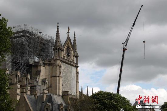 当地时刻4月27日,巴黎圣母院应急保护作业赶紧进行。保护人员为在大火中严峻损毁的圣母院顶部加装防雨设备,并为圣母院外部一些比较软弱的结构加装防护网等设备。中新社记者 李洋 摄