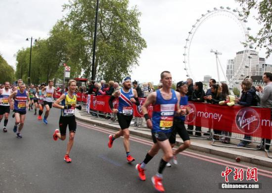 """资料图:第39届伦敦马拉松比赛。图为选手们在比赛中经过伦敦标志性建筑""""伦敦眼""""。 中新社记者 张平 摄"""