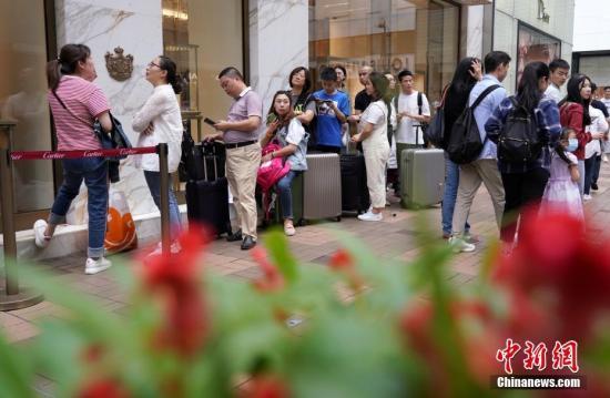 五一假期,香港一家品牌店门口,顾客排起长龙。中新社记者 张炜 摄