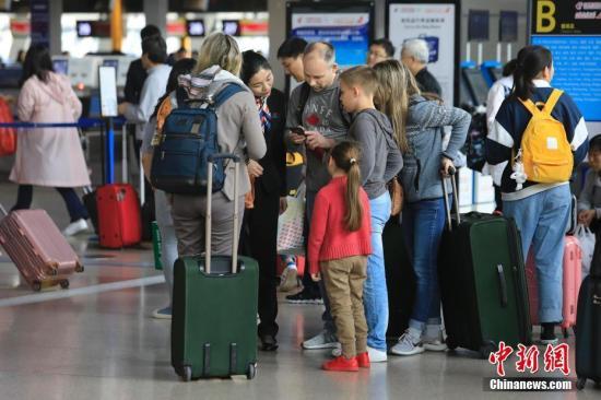 资料图:5月4日,旅客在上海浦东国际机场T1航站楼出发层,办理登记手续前往自己的目的地。 殷立勤 摄