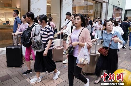 """资料图:""""五一""""小长假期间,民众在商业街购物。中新社记者 张炜 摄"""