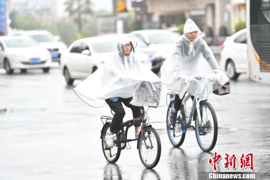 市平易近减薄衣物骑止正在路擅埽 张浪 摄