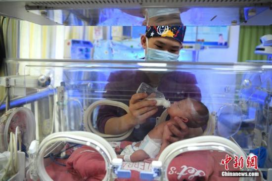 资料图:护士正在为婴儿喂奶。 陈超 摄