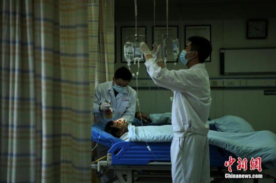 """5月8日,男护士们正在自己岗位上忙着为不同的患者进行护理。""""5·12""""国际护士节临近,<a target='_blank' href='http://www.chinanews.com/' >中新网</a>记者走进陆军军医大学新桥医院血液透析中心、骨科、急诊监护室、手术室、消化内镜室、儿科新生儿室,探访科室男护士们的日常护理工作。据悉,陆军军医大学新桥医院在2016年成立专门的男护士工作小组,男护士比例占医院护士总数的10%。图为急诊监护室的男护士正在为病人护理。陈超 摄"""