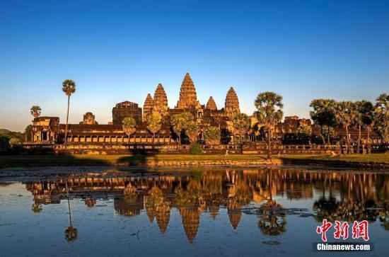 """柬埔寨始建于公元12世纪,由吴哥王朝国王苏耶跋摩二世举全国之力耗时35年建造完成,是世界上最大的庙宇。后因吴哥王朝衰败,吴哥窟被遗弃,并被茂密的雨林所淹没,直到1861年才被一名法国博物学家""""发现""""。 如今的吴哥窟依然保存有较完整的雄伟建筑以及精美的浮雕,使得人们得以窥探古代吴哥王朝登峰造极的宗教与艺术。 吴哥窟于1992年被联合国教科文组织列入世界文化遗产名录,再加上身处东方密林之中被意外发现的经历,更为其平添了一抹神秘的色彩,因而成为游客必到的旅游胜地。 图为吴哥窟资料图片。lt;a target='_blank' href='http://www.chinanews.com/'gt;中新社lt;/agt;发 黄力生 摄 图片来源:CNSPHOTO"""