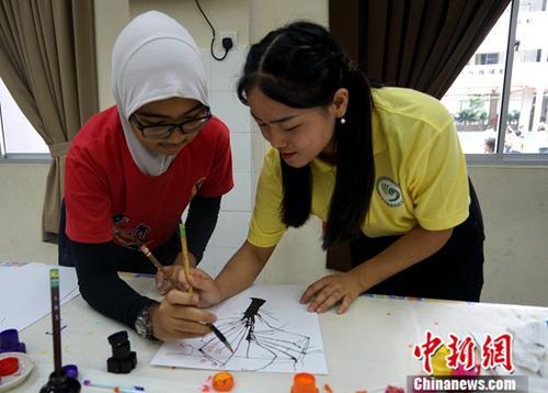 5月15日,马来西亚吉隆坡侨南国民型华文小学校园内,马来西亚世纪大学孔子学院的中国老师正在辅导马来裔学生学习中国水墨画。中新社记者 陈悦 摄
