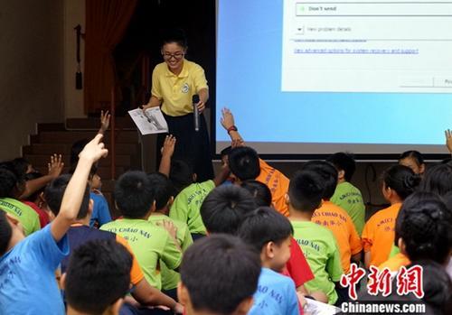 5月15日,马来西亚吉隆坡侨南国民型华文小学校园内,来自世纪大学孔子学院的老师正在辅导同学们学习诗歌。中新社记者 陈悦 摄
