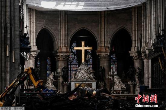 资料图:当地时间2019年5月15日,法国巴黎,外媒称,巴黎最著名的地标之一——巴黎圣母院在遭遇大火近一个月后,其内部被损毁的视频才得以公开。据英国《每日电讯报》网站5月15日报道,大火烧毁了近三分之二的屋顶,导致屋顶和尖塔上有大约几百吨的铅熔化。报道称,工人们穿着防护服,戴着面罩,正在清理废墟,包括散落在哥特式大教堂地板上的烧焦的横梁。 报道称,不过,在这些满目疮痍的景象中,作为希望的象征,巴黎圣母院一些最具标志性的特征没有遭到火焰的吞噬,其中包括部分玫瑰花窗。