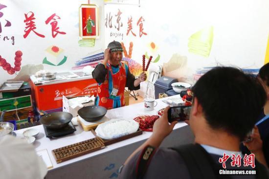5月16日,亚洲美食节在北京奥林匹克公园中心区设置的主会场迎客,该美食节是亚洲文明对话大会的重要配套活动。图为北京传统叫卖吸引观众。<a target='_blank' href='http://www.yongnian.com/'>中新社</a>记者 富田 摄
