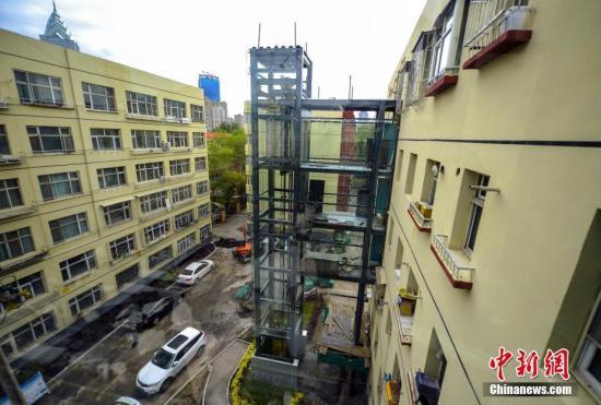 """5月17日,新疆乌鲁木齐市林业和草原局(市园林管理局)家属区6号住宅楼新加装的两部外挂式玻璃幕墙电梯主体工程已完工并完成测试,目前正在进行内部装修,将于近期投入使用。据介绍,为老旧楼房加装电梯是2019年乌鲁木齐市民生建设十大实事之一的""""便利工程"""",计划将在全市范围内选取具备加装条件的住宅小区,实施500部电梯的加装工作。中新社记者 刘新 摄"""