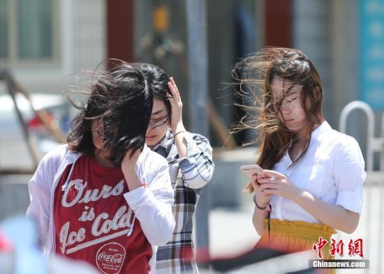 5月20日,北微风气候持,市平易近正在风中出止。a target='_blank' href='http://www.chinanews.com/'种孤社/a记者 贾天怯 摄