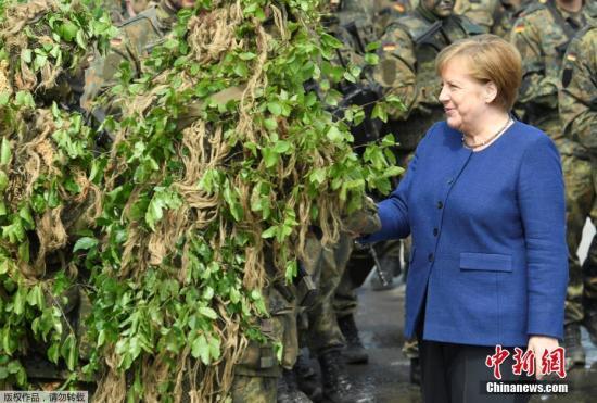 当地时间5月20日,德国总理默克尔在德国北部城市蒙斯特视察驻当地北约快速反应部队。默克尔当天上午在蒙斯特观看了北约快速反应部队下属的高级戒备联合特遣部队现场演示。约400名军人以及战机、直升机、坦克、装甲车等参与演示。图为默克尔与参加演习的狙击手握手。