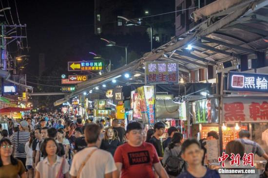5月20日,入夜后的台湾台中逢甲夜市热闹非凡,游客鱼贯而入。这一夜市位于逢甲大学周边,是台中著名商圈之一,除了售卖食品和饮品的档口,还有不少经营服饰、娃娃机的商家,满足游客吃喝玩购的需求。 洪坚鹏 摄