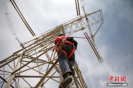"""""""电力天路""""检修现场,输电专业人员正登塔消除缺陷。朱毅然 摄"""