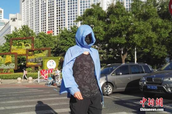 5月21日,北京市民在烈日下出行。中新社记者 贾天勇 摄