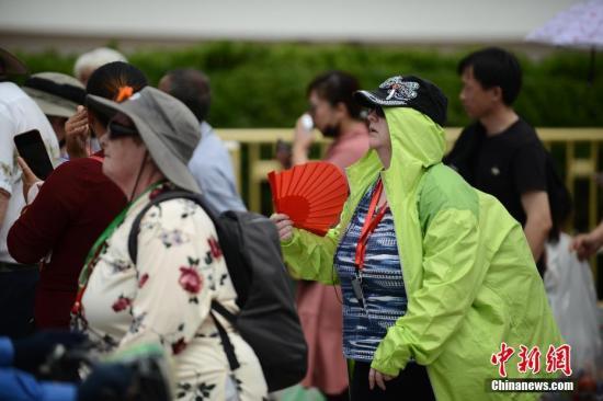 """5月22日,在天安门前游玩的外国游客""""花式""""遮阳。中新社记者 张兴龙 摄"""