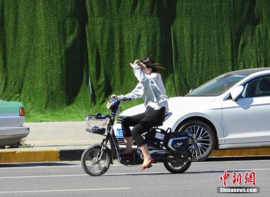 5月22日,河南郑州,街头出行的市民用手遮挡阳光。中新社记者 王中举 摄