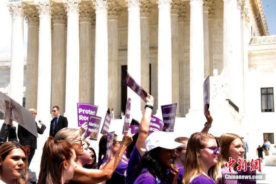 """资料图:地方时间5月21天,多次百名抗议者聚集在位于华盛顿的美国联邦最高人民法院门前,抗议近期美国多只州通过的查禁堕胎法令。示威者举在写起""""维护安全、官方堕胎""""、""""自身之人我做主""""、""""人流是人权""""相当口号的牌子,高喊""""消除禁令""""。中新社记者 沙晗汀 拍摄"""