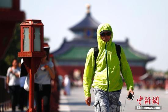 5月23日,一游客遮阳出行。/p中新社记者 富田 摄