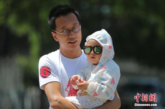 5月23日,一名家长抱着孩子在烈日下的北京街头。中新社记者 杨可佳 摄