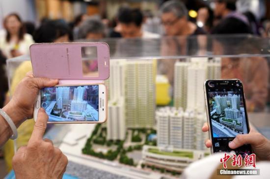 资料图:市民争相用手机拍摄居屋楼盘模型。/p中新社记者 张炜 摄