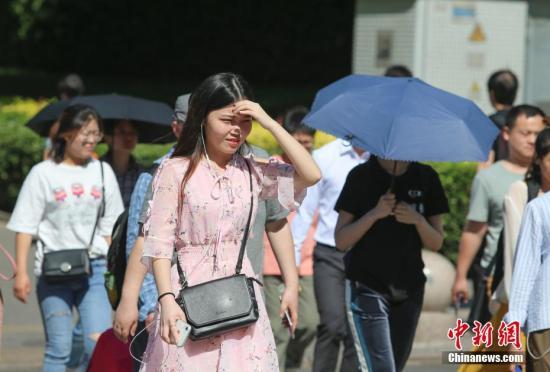 资料图:民众在高温晴晒天气中出行。中新社记者 贾天勇 摄