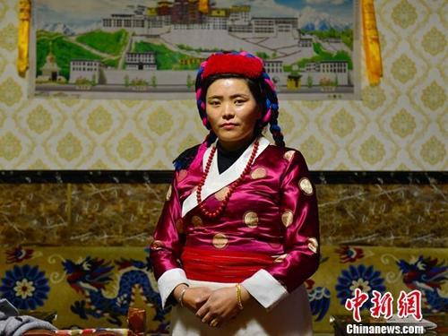 """38岁的桑姆是门巴族人,她在喜马拉雅山脉东段的一条南伸大峡谷内经营着一家只有3间客房的家庭旅馆,每年4至10月是那里的""""旅游季"""",也是她最忙碌的时候。门巴族有1万余人,在中国属人口较少民族,主要分布于西藏山南、林芝等地,酒歌、舞蹈、服饰、手工艺等是他们独具的特色文化。图为5月20日,38岁的桑姆身着传统服饰在她开设的家庭旅馆内。/p中新社记者 江飞波 摄"""
