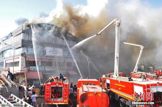 当地时间5月24日,印度古吉拉特邦苏拉特市一培训中心发生大火。据报道,大火已造成至少19名人遇难,遇难者大多是在楼内上课的学生,另有多人受伤。图为消防车在或场外向楼内喷水。