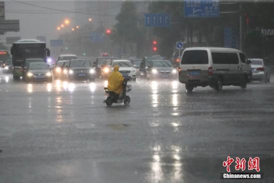 資料圖:降雨天氣中一名市民穿著雨衣騎車出行。<a target='_blank' href='http://www.bedrijfsauto.net/'>中新社</a>記者 賈天勇 攝