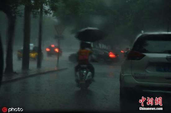 """5月26日,北京迎来明显降雨天气,为京城""""降温"""",街头市民撑伞出行。图片来源:Icphoto"""