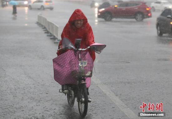材料图:北一位市平易近正在雨中骑车出止。a target='_blank' href='http://www.chinanews.com/'种孤社/a记者 贾天怯 摄