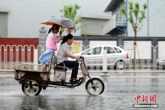 材料图:公众正在雨中出止。a target='_blank' href='http://www.chinanews.com/'种孤社/a记者 张兴龙 摄