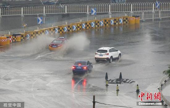 """5月26日,北京迎来明显降雨天气,为京城""""降温"""",街头市民撑伞出行。图片来源:视觉中国"""