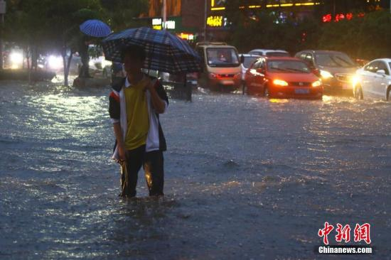 5月25日,江西省瑞昌市呈现短时强降水气候,当日17时至19时,两小时内降雨量高达54.8毫米,部分降水71.5毫米,城区部分路段积水严峻,市民在雨中困难出行。中新社发 魏东升 摄