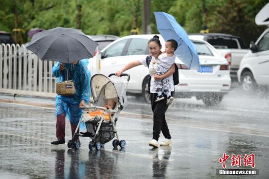 材料图:市平易近撑伞出止。a target='_blank' href='http://www.chinanews.com/'种孤社/a记者 张兴龙 摄