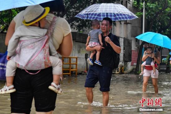5月29日,广州番禺,市民涉水出行。当日,广州出现了大到暴雨、局部大暴雨天气,市区多个路段出现道路水浸、通行缓慢等情况,来往行人纷纷卷起裤管淌水过街。中新社记者 陈骥旻 摄
