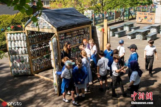 """资料图:2019年6月4日,在英国兰开夏郡阿克拉辛顿,St Marys RC小学的学生们用3,000个塑料瓶装造了间""""教室""""。 项目开始前,孩子们将回收的两吨塑料制成了""""砖头"""",完工后的这间户外教室包含阅读区,配有桌椅,还附带一个完全由塑料瓶制成的小屋,小朋友们用木勺将玻璃纸和塑料包装捣碎,塞进从各地收集来的的两升瓶子里搭建小屋,每塑料瓶""""砖块""""重700克。 图片来源:ICphoto"""