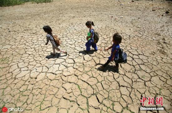 近日,印度许多地区的气温逼近50摄氏度,接连不断热浪来袭触动了供水短缺的警告。据报道,印度气象局表示,西部沙漠省份拉吉斯坦(Rajasthan)5月31日高温达到49.6摄氏度,是印度2019年至今最热的一天。印度西部、北部和南部许多省份的气温徘徊在47摄氏度上下。在首都新德里,因气温达到47摄氏度,气象局发布极端天气红色警报。图为儿童行走经过干涸的池塘,土地龟裂。