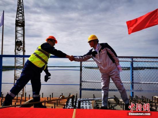 资料图:中俄黑龙江大桥上,双方建设工人安装合龙螺栓并握手祝贺。邵国良 摄