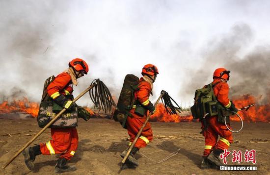 6月4日,甘肃省森林消防总队张掖市支队开展实地灭火演练。图为消防员手拿灭火工具开展火灾扑救演练。张小军 摄