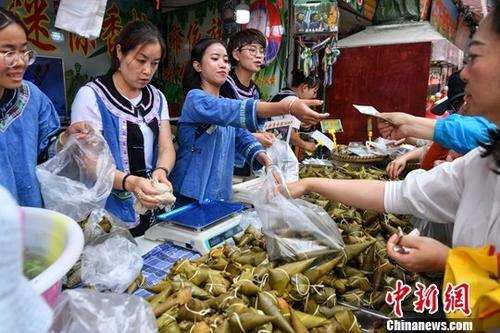 資料圖:6月5日,商販身穿少數民族服飾售賣特色粽子。<a target='_blank' href='http://www.bedrijfsauto.net/'>中新社</a>記者 任東 攝