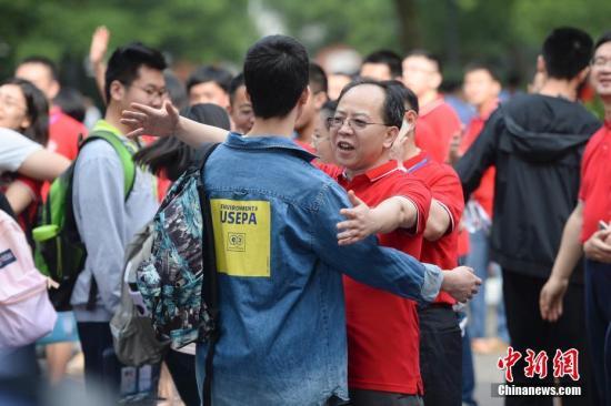 6月7日,长沙市一中考点前考生与先生拥抱。当日,2019年全国高考正式拉开大幕。中新社记。者 杨华峰 摄