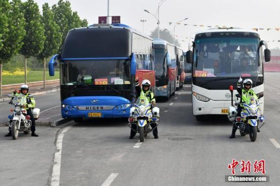 资料图:交警驾驶摩托为高考考生大巴车开道。中新社记者 翟羽佳 摄