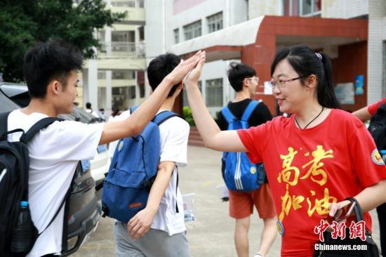 """6月7日,2019年高考启幕。在广西柳州市柳江中学考点,考生们头戴红绳、穿着印有""""鸿运当头考的都会""""字样的衣服、举着""""必胜,加油""""的牌子,一路唱着歌步入考场,以各式各样的方式为自己鼓劲加油。今年广西高考考生规模达46万,较去年增幅6万余人,总报考人数再创历史新高。图为老师穿着印有""""高考加油""""字样的服装,与学生击掌。朱柳融 摄"""