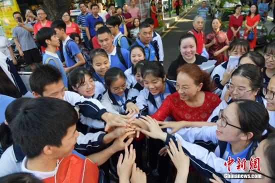 6月7日,在2019年全国高考深圳市福田中学考点,老师与考生一起加油。中新社记者 陈文 摄